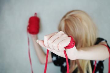 Mujer en su taller de costura con lana roja