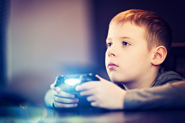 The boy is playing a TV game