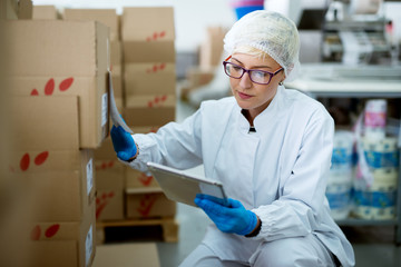 Young beautiful focused female worker in sterile cloths using a tablet to check correction of inventory in factory storage room.