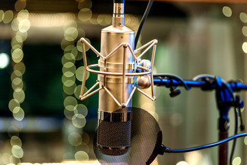 A tube microphone on a stand with pop filter in a recording studio with sound absorbers and fairy LED lights