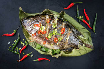 Traditional Thai barbecue tilapia fish staffed with coriander and chili as top view on a banana leaf