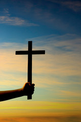 Silhouette of hand holding cross on sunset background
