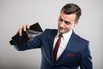 Attractive business man showing his empty wallet