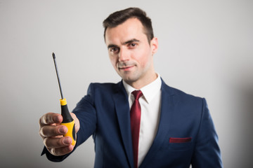 Selective focus of business man showing one screwdriver