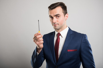 Portrait of business man showing one screwdriver