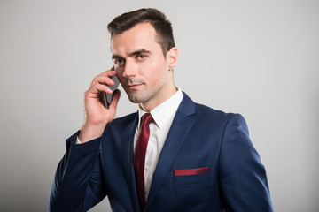 Attractive business man talking at smartphone