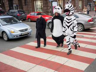 Men dressed as a zebra and a panda, who pose for pictures with tourists, walk on a pedestrian crossing, in central Kiev