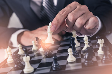 the abstract image of the businessman take a checkmate on the chess board during the chess game. the concept of intelligence and education.