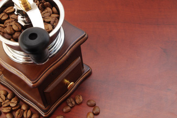 Vintage coffee grinder and arabica coffee beans on wooden table with copyspace