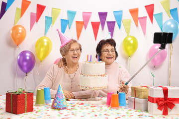 Two cheerful elderly women with party hats and a birthday cake taking a selfie