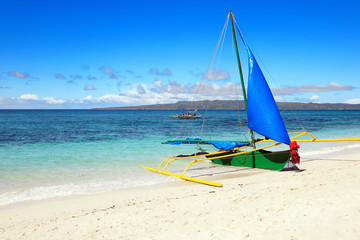 Outrigger sailboat stranded on white sandy beach, Boracay Island, Philippines