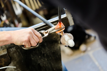 Glass artist works on seagull sculpture made from hot glass