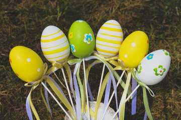 Painted Easter eggs with ribbon decorations in a spring garden