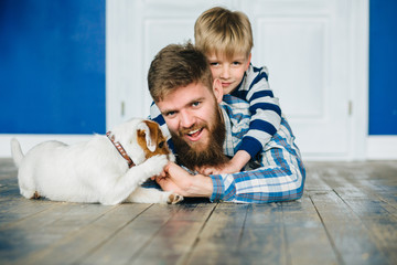 Portrait of happy beard father and his preschooler son lying on floor, playing piggyback with adorable jack russell terrier puppy at empty home interior. Pet lover, fatherhood and childhood concept.