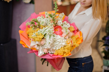 Girl holding a beautiful bright bouquet of white lilacs and roses