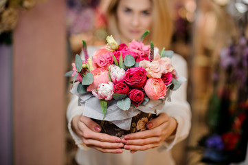 Girl holding a beautiful bouquet of different colour roses