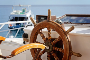 yacht's wooden steering wheel in the blue sea