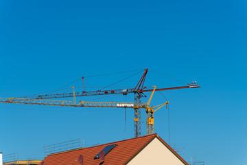 Baustelle mit Kran einer Wohnhausanlage mit Besuch eines Storchenpaar auf dem Kran-Ausleger