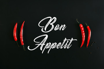 bon appetit inscription and red chili peppers on black