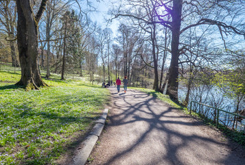 Unrecognizable people enjoying a walk and spring atmosphere in the city park along Motala river in Norrkoping. Norrkoping is a historic industrial town in Sweden.