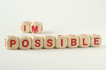 The word possible written with wood blocks - Changing impossible into possible concept
