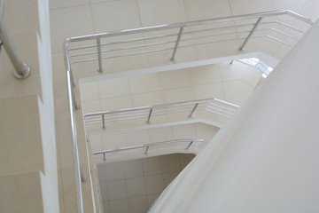 Metal railing of a multi-tiered staircase. Perspective.