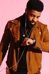 Cool African American man with beard and headphones checking his watch, isolated on pink studio background