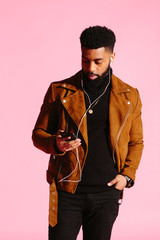 Cool man with beard and headphones, texting and looking at the phone in his hand, isolated on pink studio background