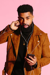 Cool African American man with beard, isolated on pink studio background