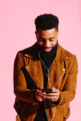 Cool African American man with beard texting, smiling and looking down at his phone, isolated on pink studio background