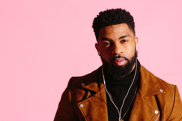 Portrait of a cool and handsome African American man with beard, isolated on pink studio background