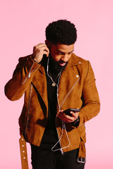 Cool African American man  looking down at phone and fixing his headphone in one ear, isolated on pink studio background