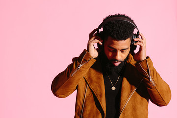 Cool African American man with beard holding headphones and looking down, isolated on pink studio background
