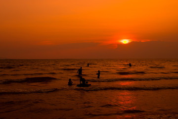People are swimming in the sea, relaxing. At sunset