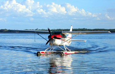 Single engine seaplane turns in the water and prepares to stop at Wooten Park, Tavares, Florida, USA.