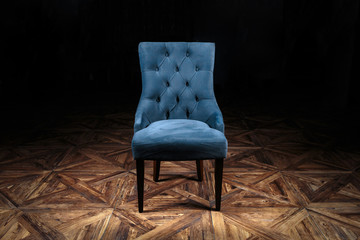 armchair, covered with gray velvet, standing in a circle of light on a wooden parquet floor with a beautiful geometric pattern on a dark background