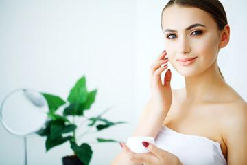 Beauty Face Care. Woman Applying Cream On Skin.