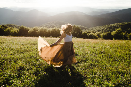 Woman with long dress running in a meadow in the mountains