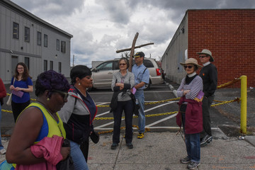 A community member carries a wooden cross on Good Friday to locations where people were killed by gun violence in Baltimore