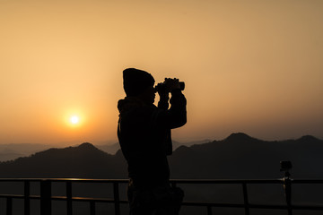 Silhouette of a photographer who was happy to shoot in the morning.