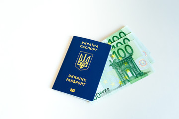 Ukraine passport with Euro Bills inside. On a white background with filler coins.