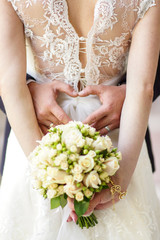 young bride in a beautiful dress holding a bouquet in hands