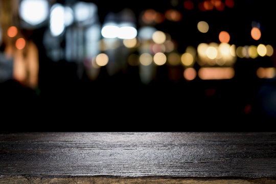 Empty wooden table platform and bokeh at night.