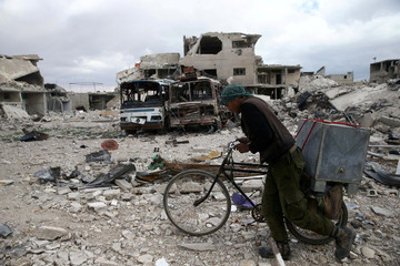 A man walks with his bicycle at a damaged site in the besieged town of Douma