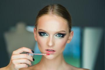 Girl apply lip gloss makeup. Girl with lip makeup, beauty