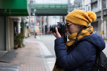 Young female photographer taking photos in city on a cloudy day wearing winter yellow and blue clothes.