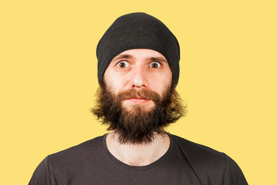Young man with beard in hat looking in camera of wide eyes. Isolated on yellow.