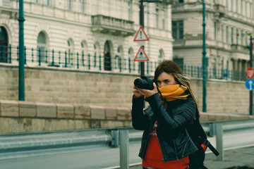 Stylish female traveler spending holiday trip on hobby taking photos of urban settings standing on street.Professional photographer cameras for making street and architecture images.