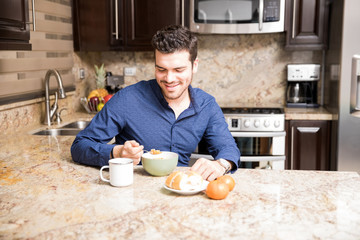 Young guy at home having breakfast