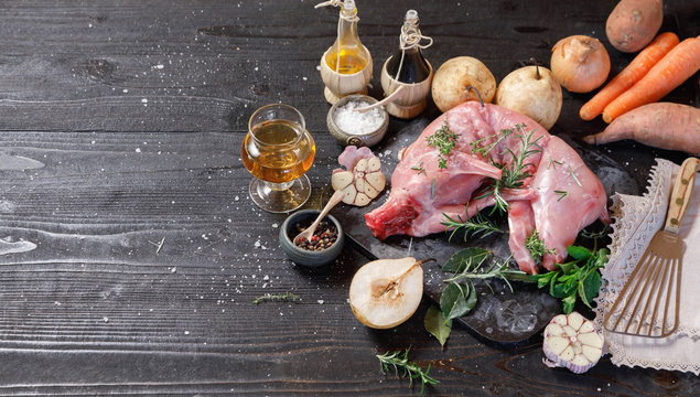 Whole Forest wild rabbit, Recipe with apple pie, Raw meat with spices and vegetables, Sea salt, red, white pepper and coriander in clay pots on an old black rustic table. copy space